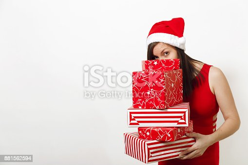 Caucasian beautiful smiling young happy woman dressed in red dress and Christmas hat hiding face behind gift boxes on white background. Santa girl with present isolated. New Year holiday 2018 concept.