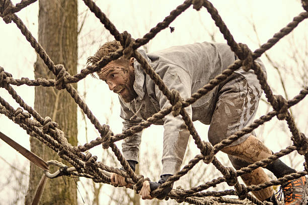 Caucasian blonde handsome man climbing obstacle during a mud run Caucasian blonde handsome man climbing obstacle during a mud run mud run stock pictures, royalty-free photos & images