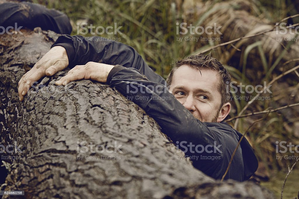 Caucasian blonde handsome man crawling over obstacle during mud run stock photo