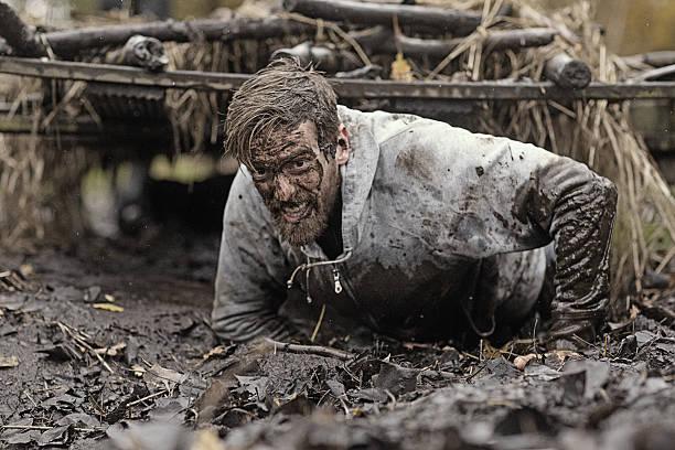 caucasian blonde handsome man crawling under obstacle during mud run - kruipruimte stockfoto's en -beelden