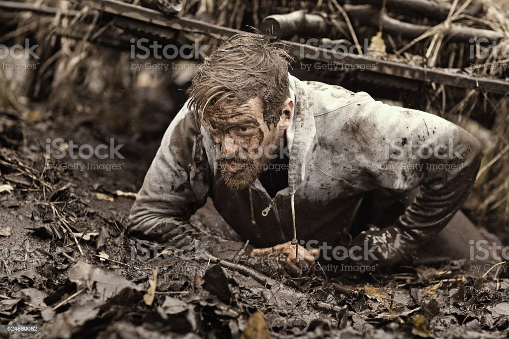 Caucasian blonde handsome man crawling under obstacle during mud run stock photo