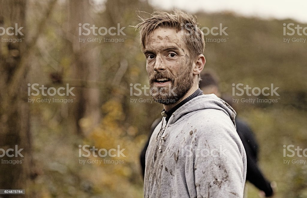 Caucasian blonde handsome man posing during a mud run stock photo