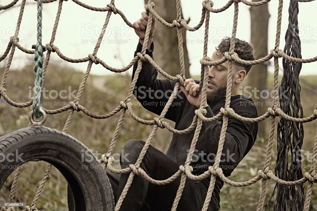 Caucasian blonde handsome young man climbing obstacle during mud run stock photo
