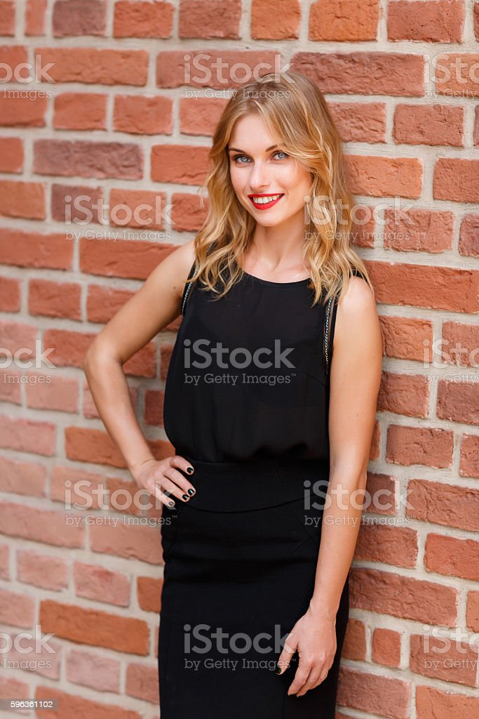 Caucasian blonde woman with bright smile on brick wall background royalty-free stock photo