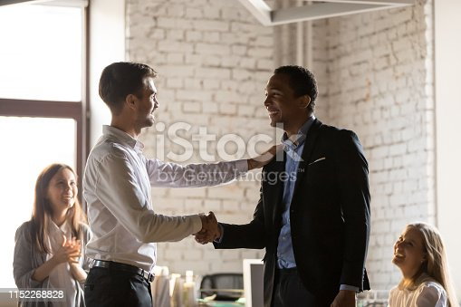 923041456 istock photo Caucasian boss congratulates african employee with promotion 1152268828