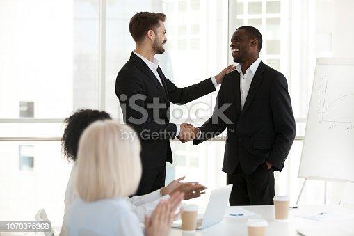 istock Caucasian boss handshake black employee greeting with success 1070375368