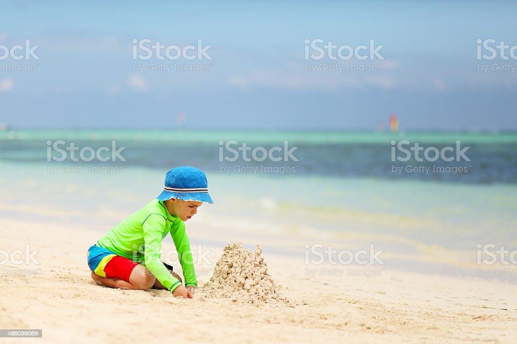 Caucasian boy building sand castle on tropical beach stock photo