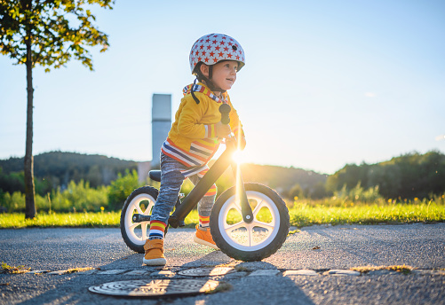 Caucasian boy with sports helmets driving balance bike outdoors on a sunny day. He is learning new skill.