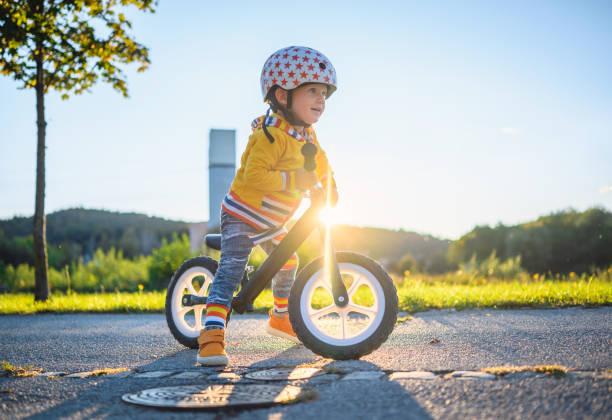 Caucasian Boy Driving Balance Bike Outdoors stock photo