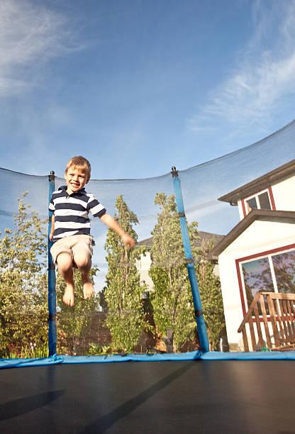 junge springen auf trampolin - gartentrampolin stock-fotos und bilder