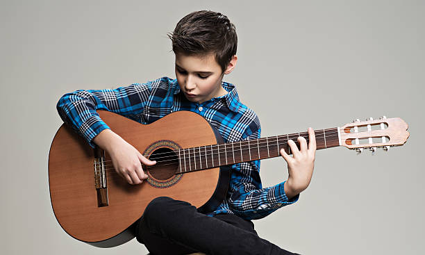 Caucasian  boy playing on acoustic guitar. – Foto