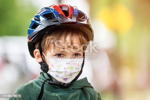 Caucasian boy posing with a protective mask, bicycle helmet looking away