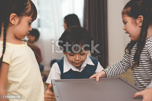 Caucasian boy scrambling for toys in plastic cupboard with her sisters. Family and children concept. Conflict and quarrel theme. Three kids in home