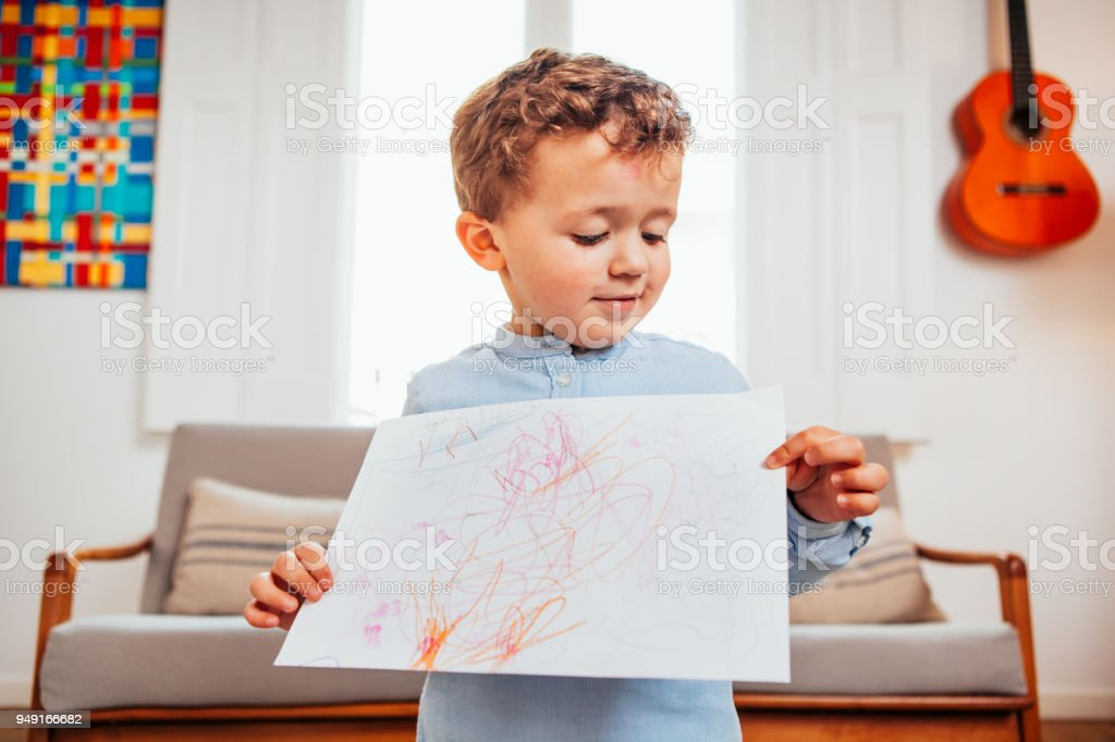 Caucasian boy showing drawing on paper stock photo