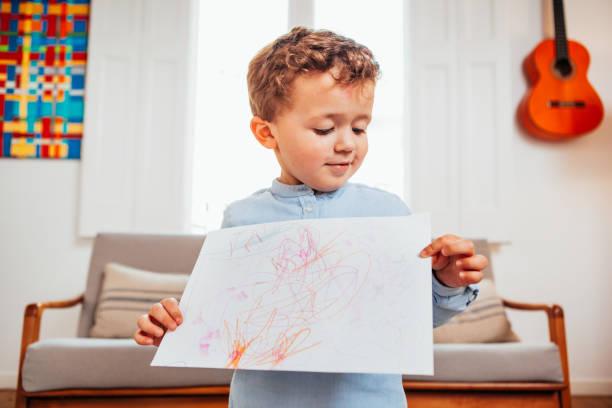 chico caucásico mostrando el dibujo sobre papel - dibujar fotografías e imágenes de stock