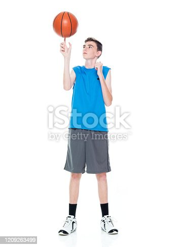 Front view of aged 12-13 years old caucasian boys basketball player spinning in front of white background and holding basketball - ball and using sports ball