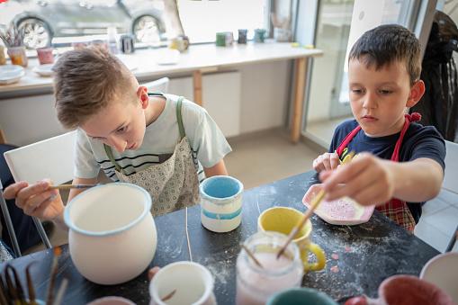 Caucasian Boys Painting Pottery