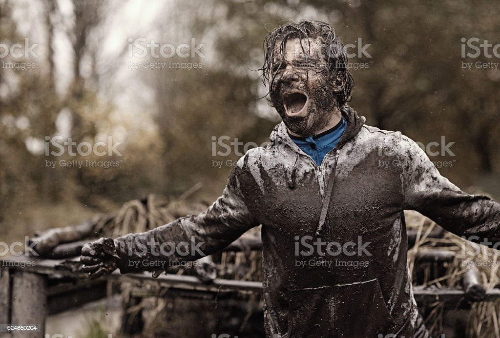 Caucasian brunette handsome man at obstacle during a mud run stock photo