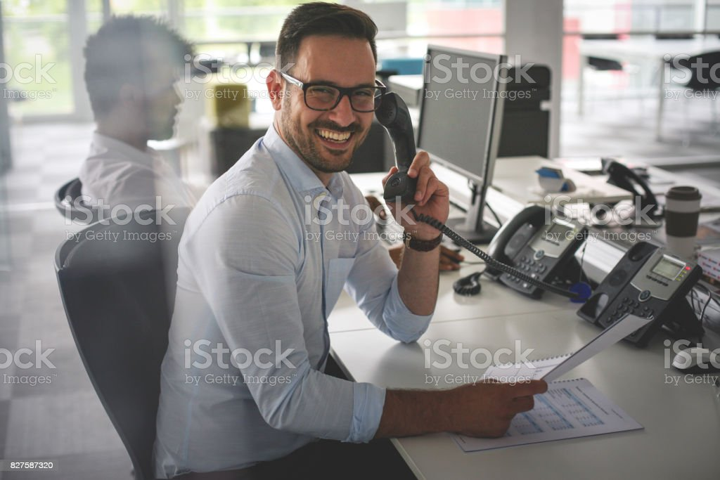 Caucasian business man having conversation on Landline phone. Business man in office. Looking at camera. stock photo