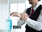 istock Caucasian business man in office using alcohol gel and rubbing hands back and forth to kill virus. protect from coronavirus or covid-19 virus world pandemic,health care and medicine concept. 1214490290