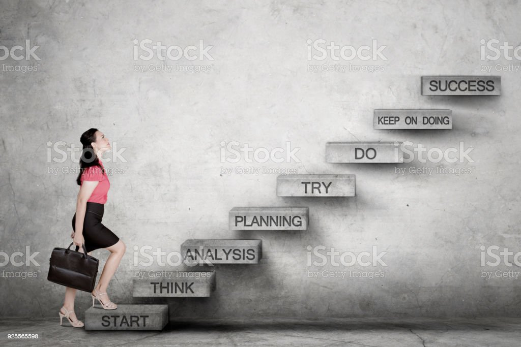 Caucasian business woman looking up ready to climb the success staircase stock photo