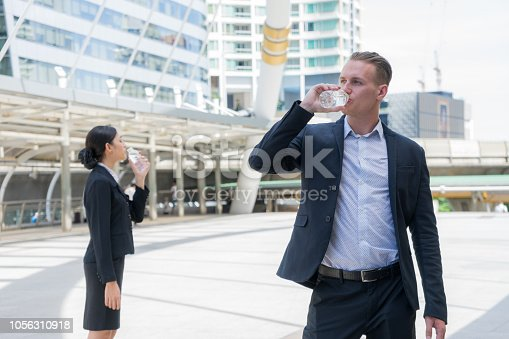 Caucasian businessman and Asian business woman standing and drinking pure mineral water from plastic bottle in hot summer day with background of city.