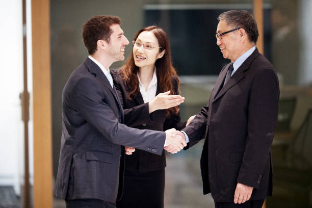 caucasian businessman closing a deal in hong kong with his asian colleagues - translator stock photos and pictures