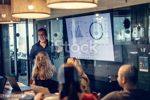 Photo of a mature adult man giving a financial presentation in a modern conference room in an office builfing.