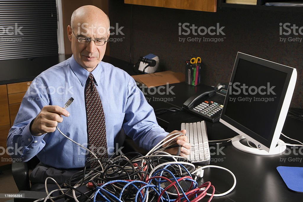 Caucasian businessman in a tangle of computer cables. royalty-free stock photo