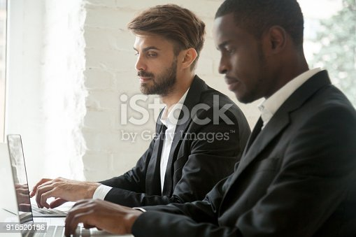 istock Caucasian businessman looking at laptop of african-american colleague stealing idea 916520186