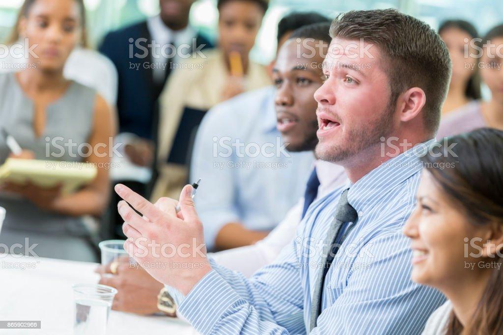 Caucasian businessman participates in panel discussion during business seminar stock photo