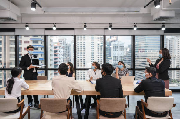 Caucasian businessman presentation of business plan on laptop at conference table, Group of business people wearing face mask meeting in modern office stock photo