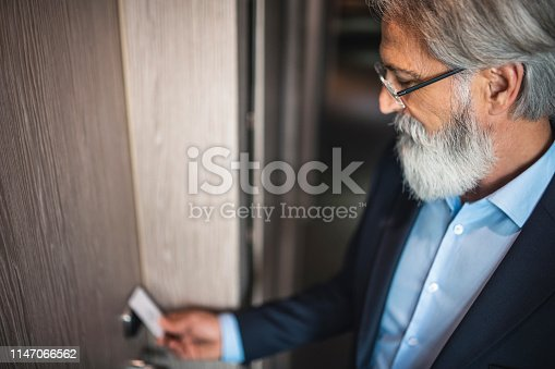 Caucasian businessman using a keyless entry card to enter his hotel room