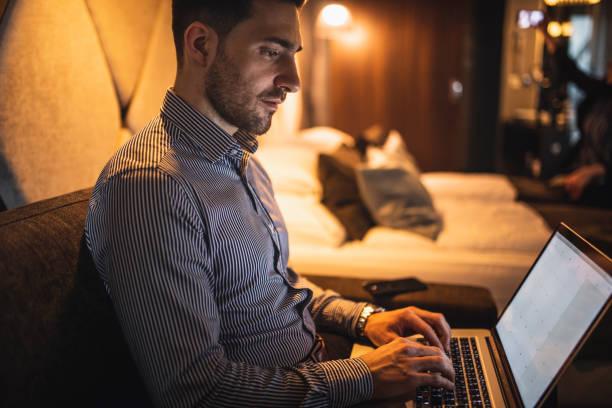 Kaukasischer Geschäftsmann mit einem Laptop in seinem Hotelzimmer – Foto