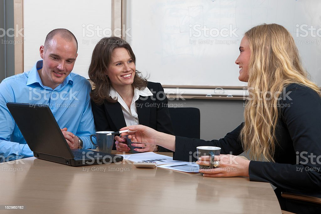 Caucasian businesswoman giving advise to couple in conference room royalty-free stock photo