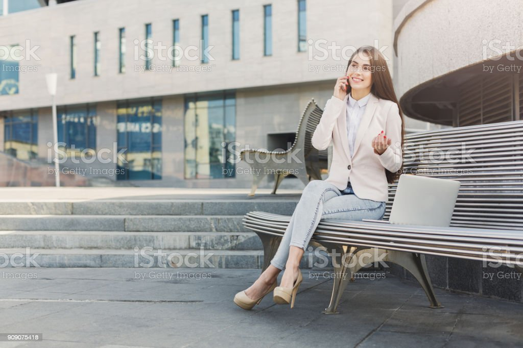 Caucasian businesswoman working with laptop outdoors stock photo