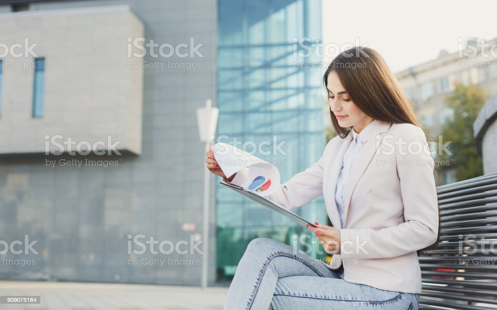 Caucasian businesswoman working with papers outdoors stock photo