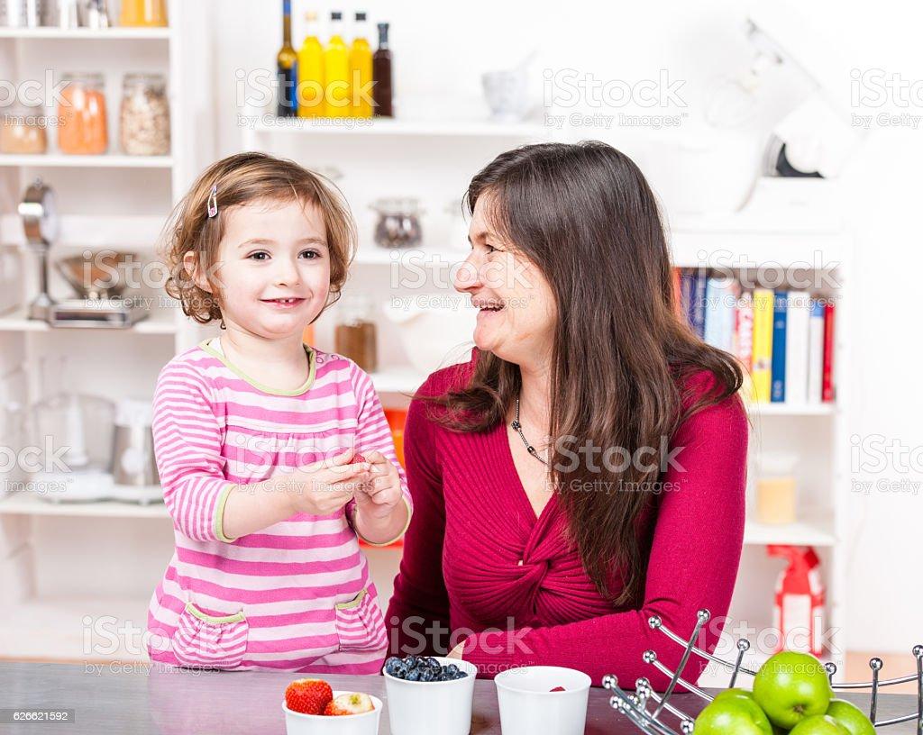 Caucasian Carer Supervising Girl Eating Fruit stock photo