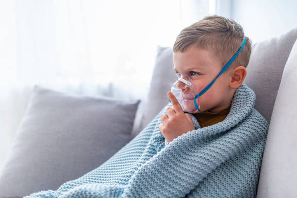 Caucasian child holding oxygen or inhaler mask at home. Little boy having inhalation for easing cough. Caucasian blonde boy inhales couples containing medication to stop coughing. Medical procedures. Inhaler. Respiratory medicine. respiratory disease stock pictures, royalty-free photos & images