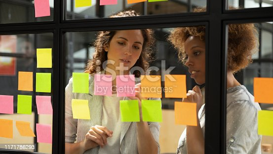 1085713886 istock photo Caucasian coach explaining task african colleague writing on sticky notes 1171786293