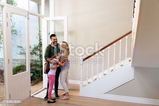 670900812 istock photo Caucasian couple and their daughter embracing in the hallway 1253626351