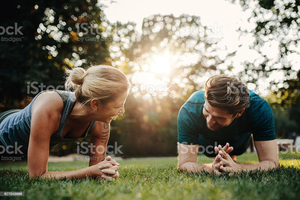 Caucasian couple doing core workout in park - Lizenzfrei Aktiver Lebensstil Stock-Foto