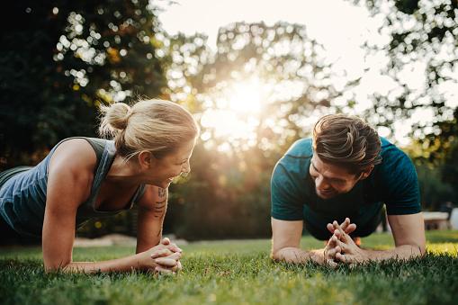 Caucasian Couple Doing Core Workout In Park Stockfoto und mehr Bilder von Aktiver Lebensstil