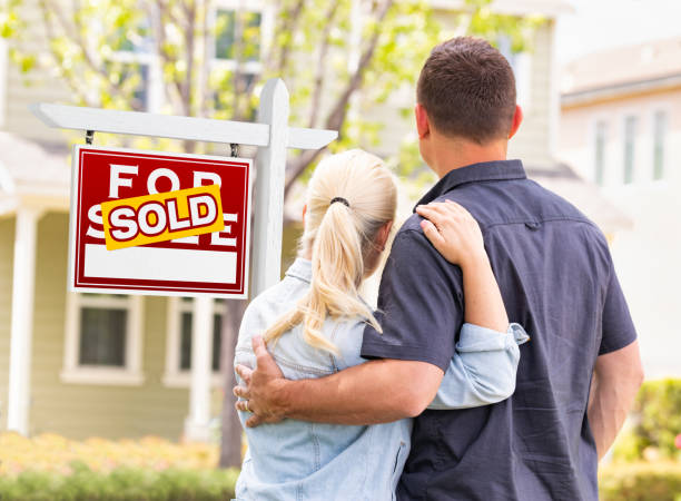 Caucasian Couple Facing Front of Sold Real Estate Sign and House stock photo
