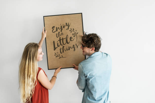 Caucasian couple hanging a frame on white wall stock photo