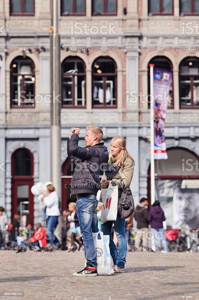 Caucasian couple having fun photographing on Amsterdam Dam Square. stock photo