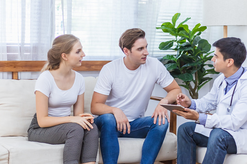 Caucasian Couple Patient Husband And Wife Visit Or Meeting Male Doctor For  Pregnant Consultation At Clinic