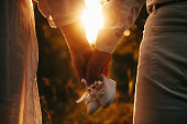 Caucasian couple posing against the sunshine while walking and holding a pair of baby shoes