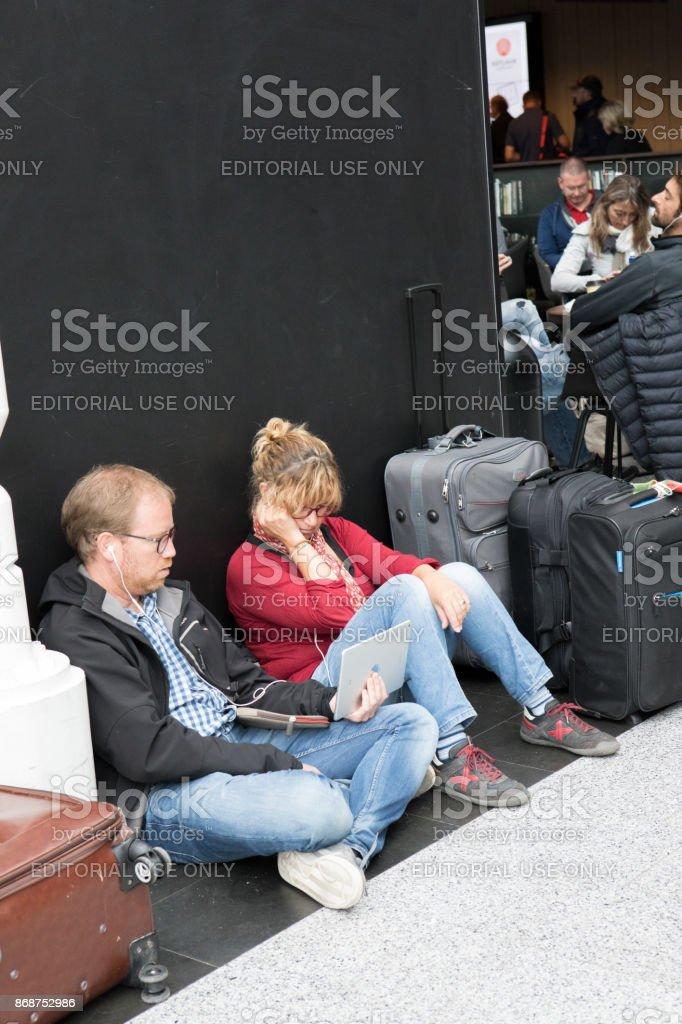 Caucasiano, sentada no chão, usando a tecnologia enquanto aguarda seu voo no Aeroporto Internacional de Keflavík, Islândia - foto de acervo