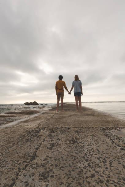 Caucasian couple standing on rock near beach stock photo